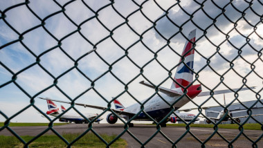 Seen through a wire fence, British Airways aeroplanes are parked at Cardiff Airport whilst unused during the Covid-19 crises.