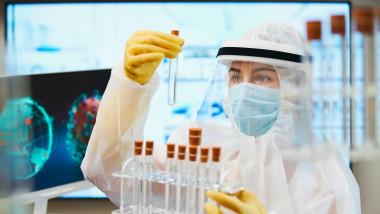 Female scientist in clean suit researching coronavirus vaccine