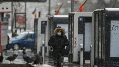 Bucharest, Romania - November 30, 2020: People wearing protective masks walk through the snow during coronavirus outbreak.