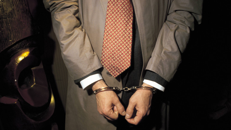 Person under arrest with handcuffs Detail of the handcuffed hands of a man under arrest