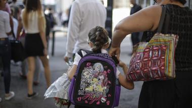 mama si fiica cu ghiozdan in spate si buchet de flori in prima zi de scoala