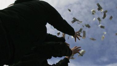 tineri arunca cu bani spre cer