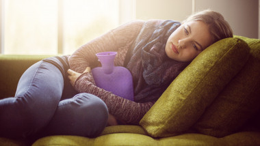 Teenage girl with hot water bottle on sofa
