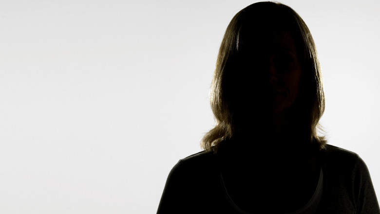 Mature woman standing in shadow against white background, portrait