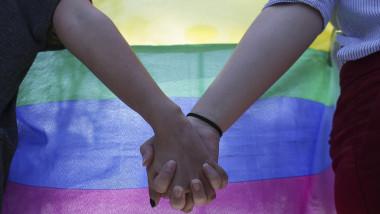 mîini înlănţuite pe fundalul steagului curcubeu, simbol al minorităţilor sexuale