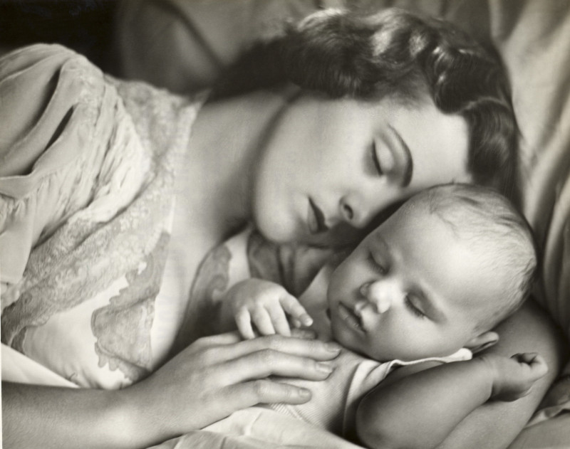 Mother holding infant in bed