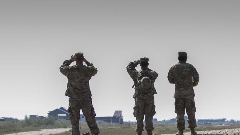 militari români se uită în zare în timpul exercițiului NATO Saber Guardian