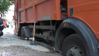 masina gunoi incastrata in asfalt