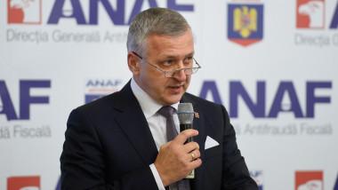 Gelu Diaconu, fostul președinte ANAF, vorbește la microfon în fața siglei ANAF