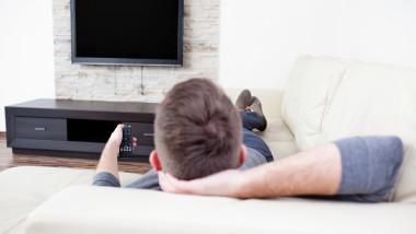 barbat se uita la televizor_shutterstock_130173635