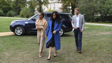 Meghan Markle și prințul Harry în fața unei mașini, pe o zonă verde, în mers