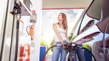 O femeie alimenteaza la pompa de benzina