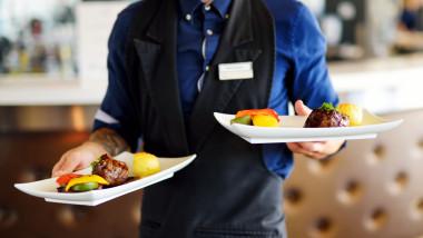 Un chelner serveste mancarea la restaurant