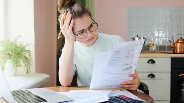 Indoor shot of young European Caucasian girl looking at financia