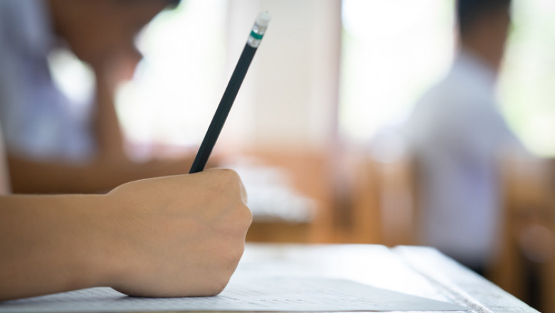 Student holding pencil writing answer of question on paper test examination