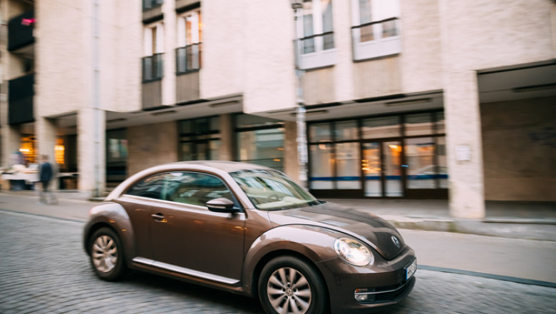 Side View Of Brown Volkswagen New Beetle Hatchback Coupe Car In