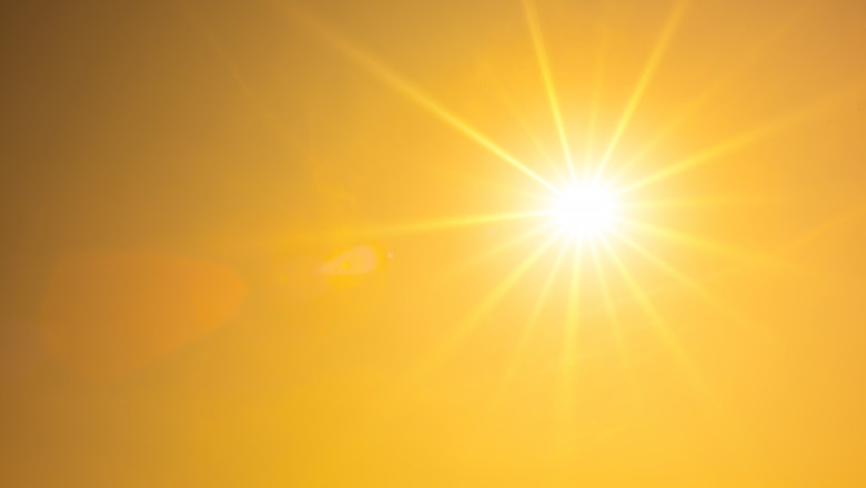 Hot summer or heat wave background, orange sky with glowing sun