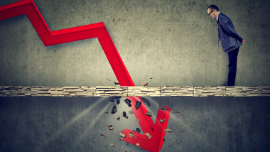 Depressed business man looking down at the falling red arrow going through a concrete floor. Fall and depreciation concept.