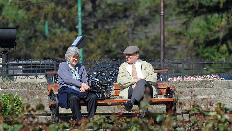 Pensionari în parc. stau pe banca