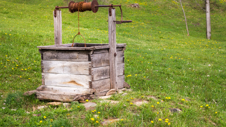 Old Wooden Fountain with Grass Hill Field