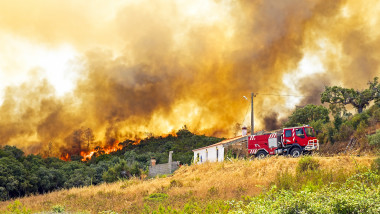 Forest fire near a rural home and fire truck in Portugal