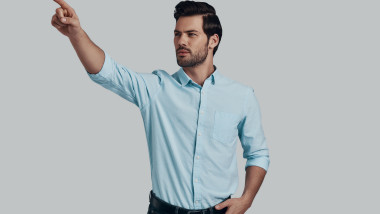 You must see this! Good looking young man pointing copy space while standing against grey background