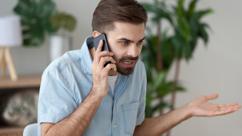 Angry man talking on smartphone solving work problem