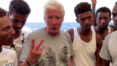 U.S. actor Gere gestures surrounded by rescued migrants aboard Open Arms rescue boat at Mediterranean sea in this screen grab taken from video