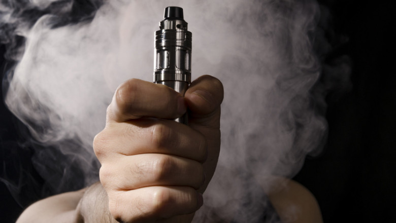 holding electronic cigarette with smoke behind.
