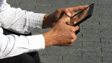 Digital tablet in male hands close-up, man in office suit sitting on the street with tablet PC