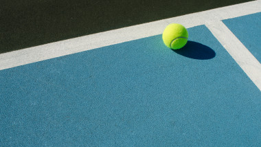 Tennis ball rests on blue tennis court
