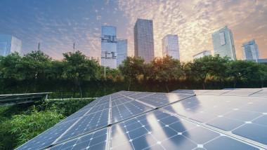 panouri fotovoltaice si cladiri de birouri inalte printre copaci