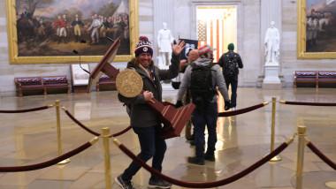 Un susținător al lui Donald Trump cară un pupitru din Capitoliu. Foto: GettyImages