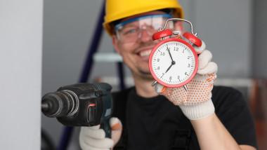 Persoană cu bormaşină şi cu un ceas deşteptător