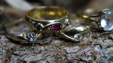 Close up of isolated old vintage golden ring with diamond and red ruby gemstone on natural tree trunk bark background