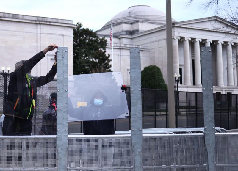 Muncitori montează garduri de protecție în centrul Washington DC înaintea ceremoniei de inaugurare a lui Joe Biden