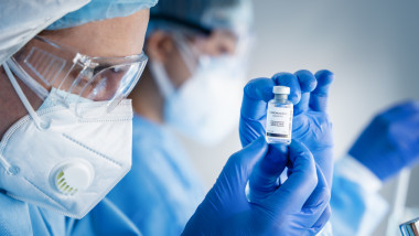 coronavirus covid-19 vaccine bottle in hands of pharmacuetical and vaccine research scientist in laboratory, coronavirus covid-19 vaccin