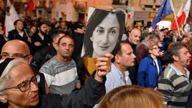 o femeie tine o poza cu daphne caruana galizia in mijlocul unei multimi