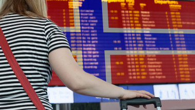 Woman looks at the scoreboard at the airport. Select a country Norway for travel or migration.