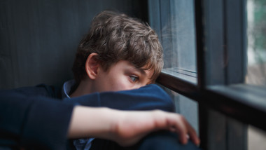 Pensive sad boy teenager in a blue shirt and jeans sitting at the window and closes his face with his hands.
