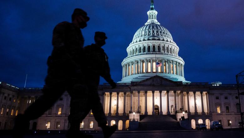 capitoliul sua iluminat noaptea cu siluetele a doi soldati trecand prin fata