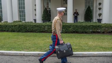 militar din Marina SUA cară valiza nucleară în fața Casei Albe