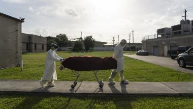 asistenţi medicali transportă pe o targă trupul unui pacient mort de COVID-19 în afara secţiei ATI a spitalului din Houston, Texas
