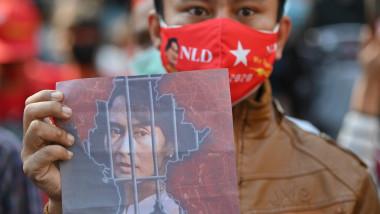 poza cu Aung San Suu Kyi tinuta in mana de un migrant