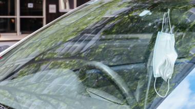 masca de protectie agatata la oglinda unei masini parcate