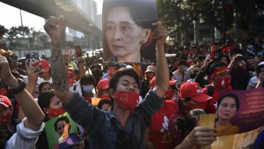 Mulțime de protestatari birmanezi, la Bangkok. Unul dintre ei ține în mână portretul lui Aung San Suu Kyi, fosta șefă a guvernului.