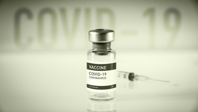 doză de vaccin anti-COVID şi o seringă pe fundal