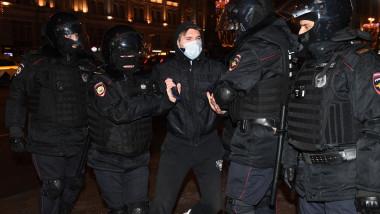 Un bărbat cu mască de protecție și îmbrăcat în negru este ținut de mâini de doi polițiști ruși îmbrăcați în echipament special.