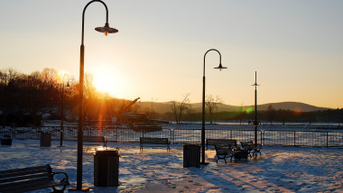 The sun sets on a park in winter