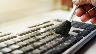 Cleaning keyboard from dust by black brush. Cleaning concept. Office cleaning.